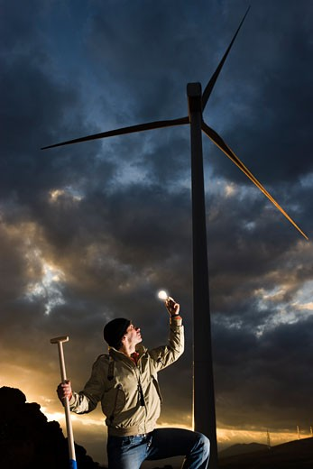 Stock Photo: 1828R-49286 Man Holding Lightbulb by Wind Turbine