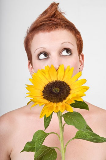 Stock Photo: 1828R-49314 Portrait of Woman Smelling a Sunflower