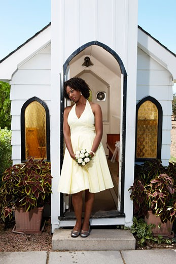 Stock Photo: 1828R-49743 Woman with Bouquet Standing in Doorway of Quaint Church, Niagara Falls, Canada