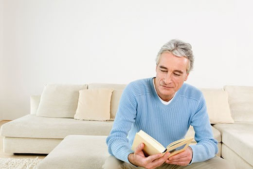 Stock Photo: 1828R-49945 Man Reading Book in Living Room