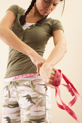 Stock Photo: 1828R-50336 Woman Measuring Her Waist