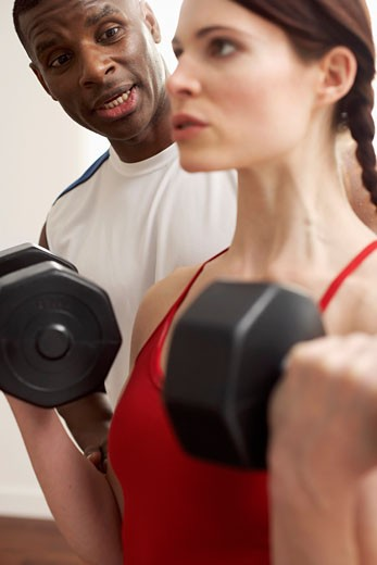 Stock Photo: 1828R-52849 Man and Woman Lifting Weights