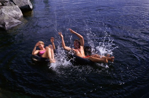 Couple Playing in Inner Tubes on Lake, Belgrade Lakes, Maine, USA    : Stock Photo