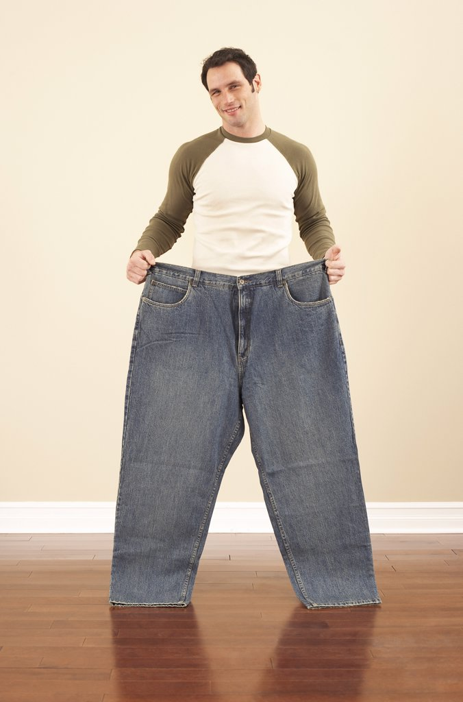 Man Holding Oversized Pants    : Stock Photo