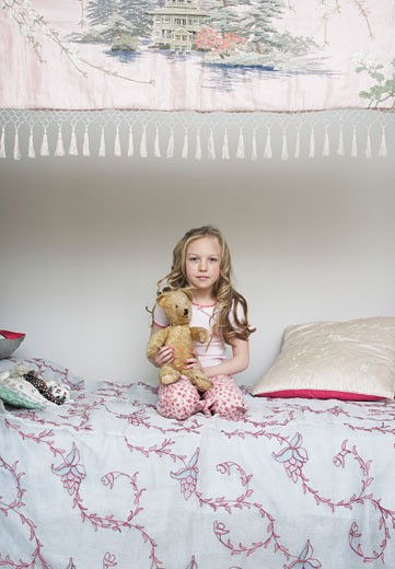 Girl Sitting on Bed, Holding Teddy Bear    : Stock Photo