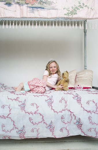 Stock Photo: 1828R-53839 Girl Sitting on Bed, Holding Teddy Bear and Wearing Tiara