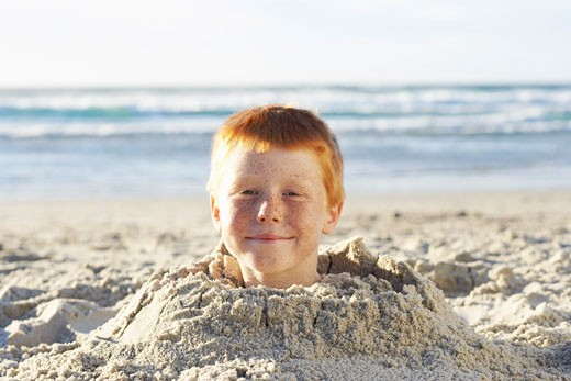 Stock Photo: 1828R-54997 Boy Buried in Sand