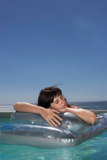 Stock Photo: 1828R-55557 Woman Floating In Pool