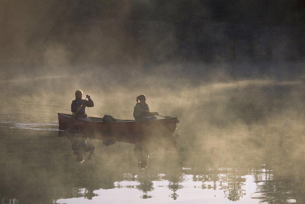 Stock Photo: 1828R-5589 Couple Canoeing on Lake with Fog, Haliburton, Ontario, Canada