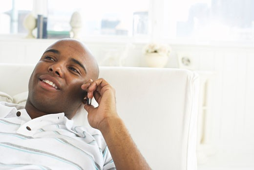 Stock Photo: 1828R-58133 Man Lying on Sofa, Talking on Cellular Phone