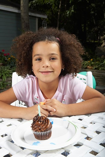 Stock Photo: 1828R-58250 Portrait of Girl with Birthday Cupcake