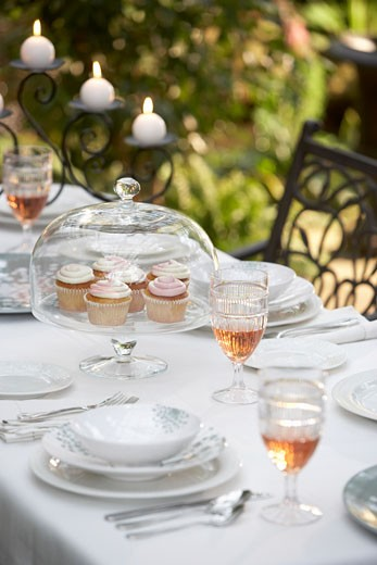 Stock Photo: 1828R-58855 Tray of Cupcakes on Table Set for Dinner Party