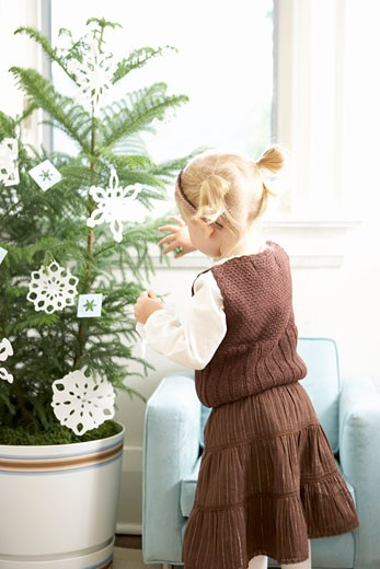 Little Girl Decorating a Christmas Tree With Paper Snowflakes    : Stock Photo