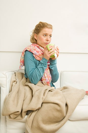 Woman holding Mug Sitting on Sofa    : Stock Photo