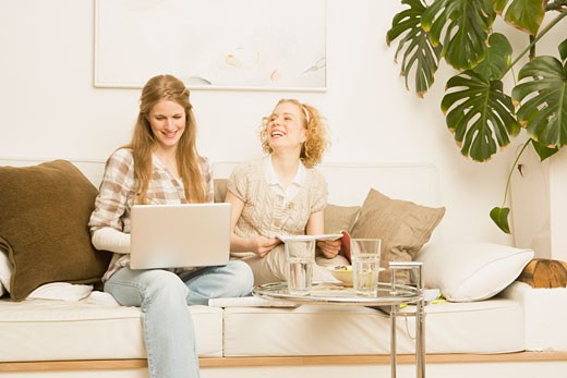 Stock Photo: 1828R-62175 Two Women Sitting on Sofa Laughing
