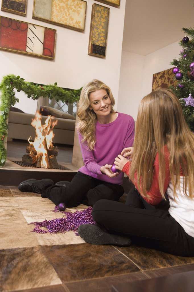 Mother and Daughter Decorating Christmas Tree    : Stock Photo