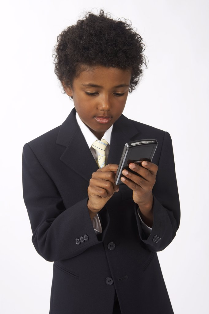 Stock Photo: 1828R-62329 Little Boy Dressed Up as a Businessman Using Cell Phone
