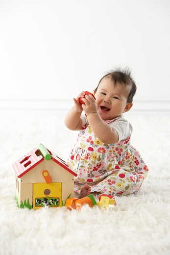 Stock Photo: 1828R-62402 Girl Playing with Shapes and House