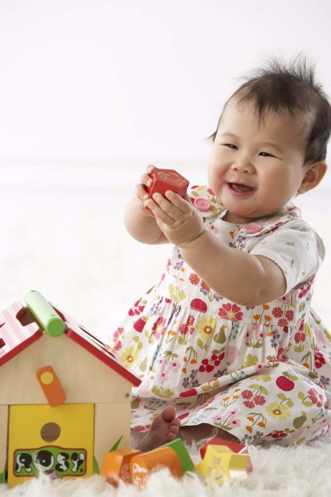 Stock Photo: 1828R-62403 Girl Playing with Shapes and House