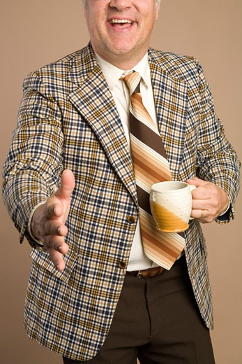 Retro Businessman With a Cup of Coffee Reaching for a Handshake : Stock Photo