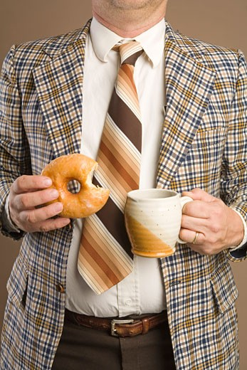 Retro Businessman Eating a Doughnut and Drinking a Cup of Coffee : Stock Photo