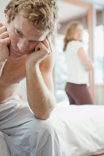 Stock Photo: 1828R-62721 Man Sitting on Edge of Bed and Woman Standing by Window in Background