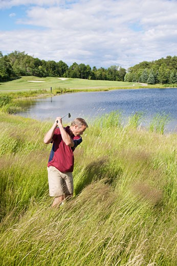 Man Golfing in Tall Grass : Stock Photo