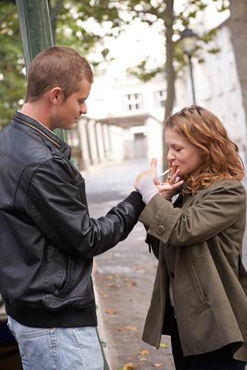 Man Lighting Woman's Cigarette : Stock Photo