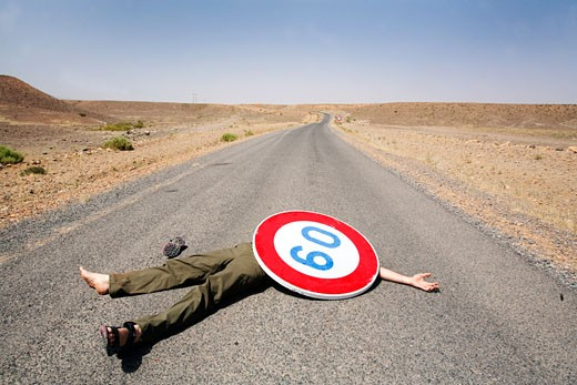 Stock Photo: 1828R-63419 Man Lying on the Road Under a Speed Limit Sign, High Atlas Mountains, Morroco
