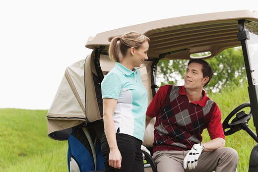 Couple with Golf Cart on Golf Course : Stock Photo