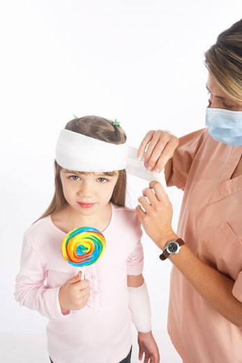 Stock Photo: 1828R-65399 Nurse Wrapping Bandage Around Girl's Head
