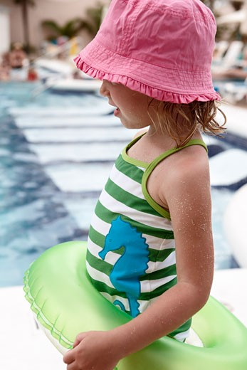 Stock Photo: 1828R-66168 Little Girl With Inner Tube Playing on Pool Deck