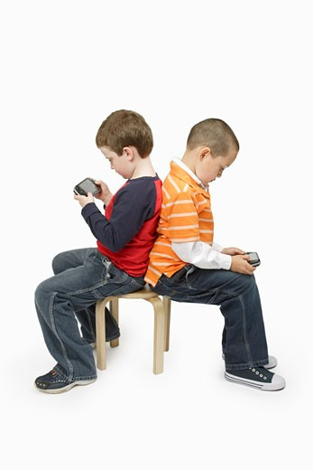 Boys with Handheld Video Games Sitting Back to Back : Stock Photo
