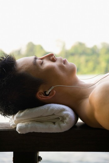 Stock Photo: 1828R-71339 Man Lying Down and Listening to MP3 Player