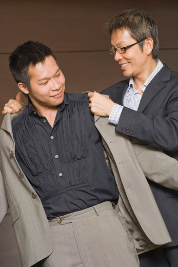 Man Helping His Partner With His Coat : Stock Photo