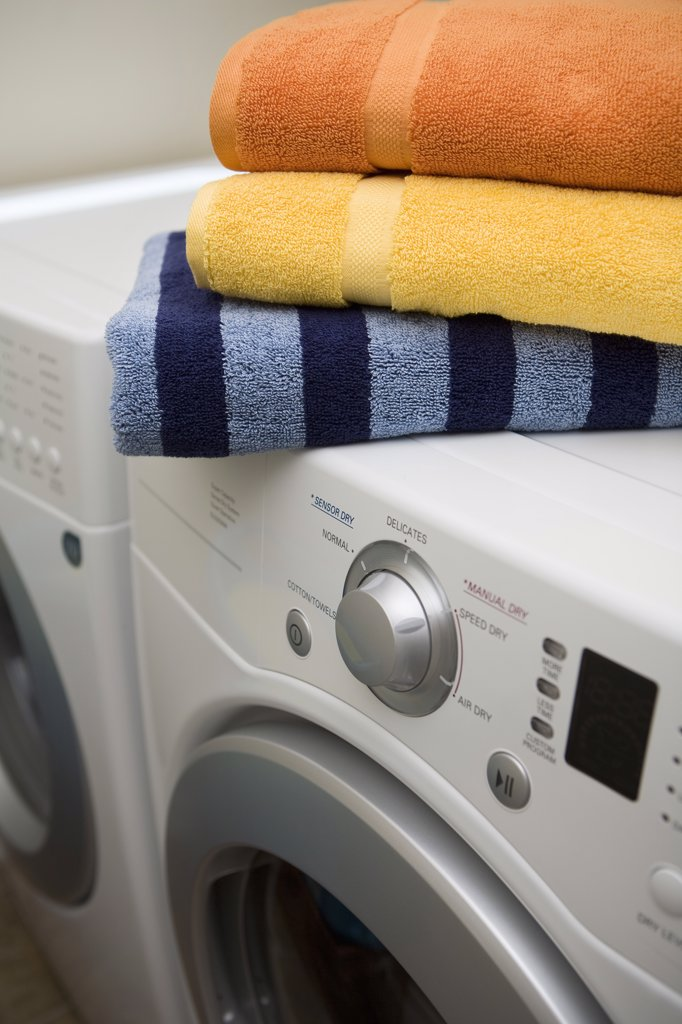 Stock Photo: 1828R-77483 stack of towels on top of washer and dryer