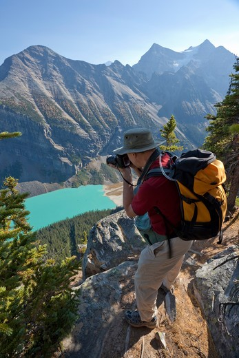 Hiker taking Pictures of Lake Louise from Big Beehive, Banff National Park, Alberta, Canada : Stock Photo