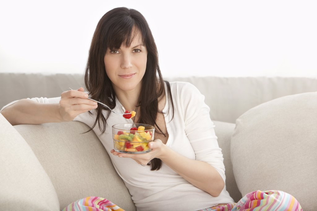 Stock Photo: 1828R-83883 Portrait of Woman Eating Fruit Salad