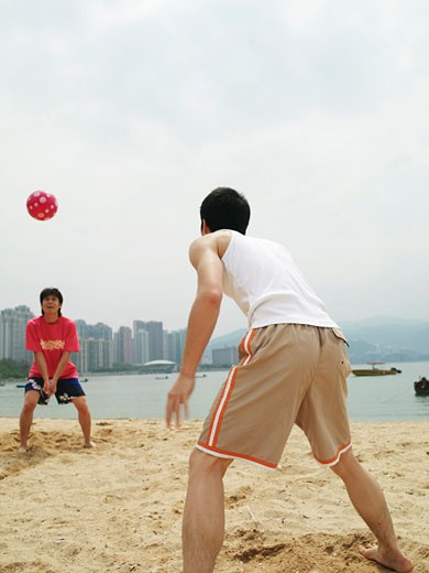 Stock Photo: 1828R-8554 Men Playing With Ball on Beach