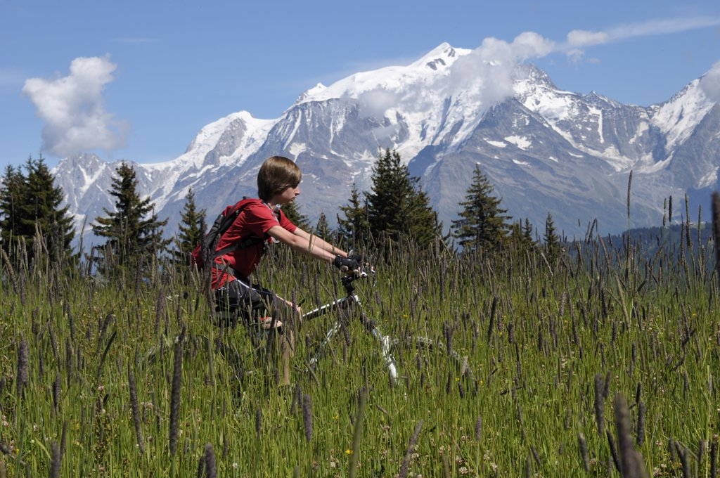 Stock Photo: 1828R-86157 Boy Riding Bicycle in Mountains, Alps, France