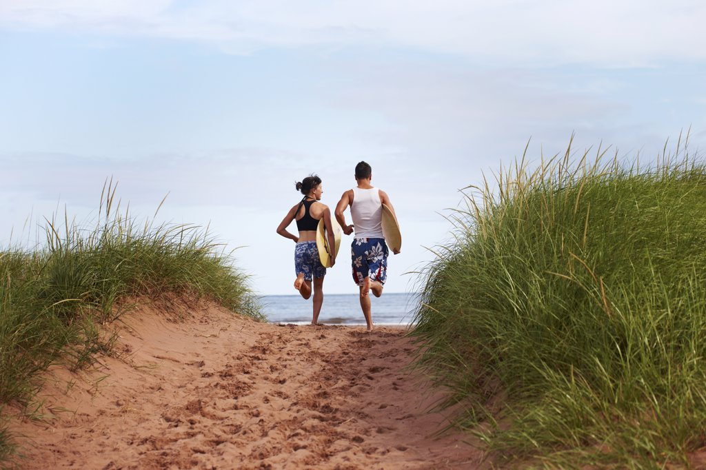 Stock Photo: 1828R-86556 Young Woman and Young Man holding Skimboards while Running to Beach, PEI, Canada
