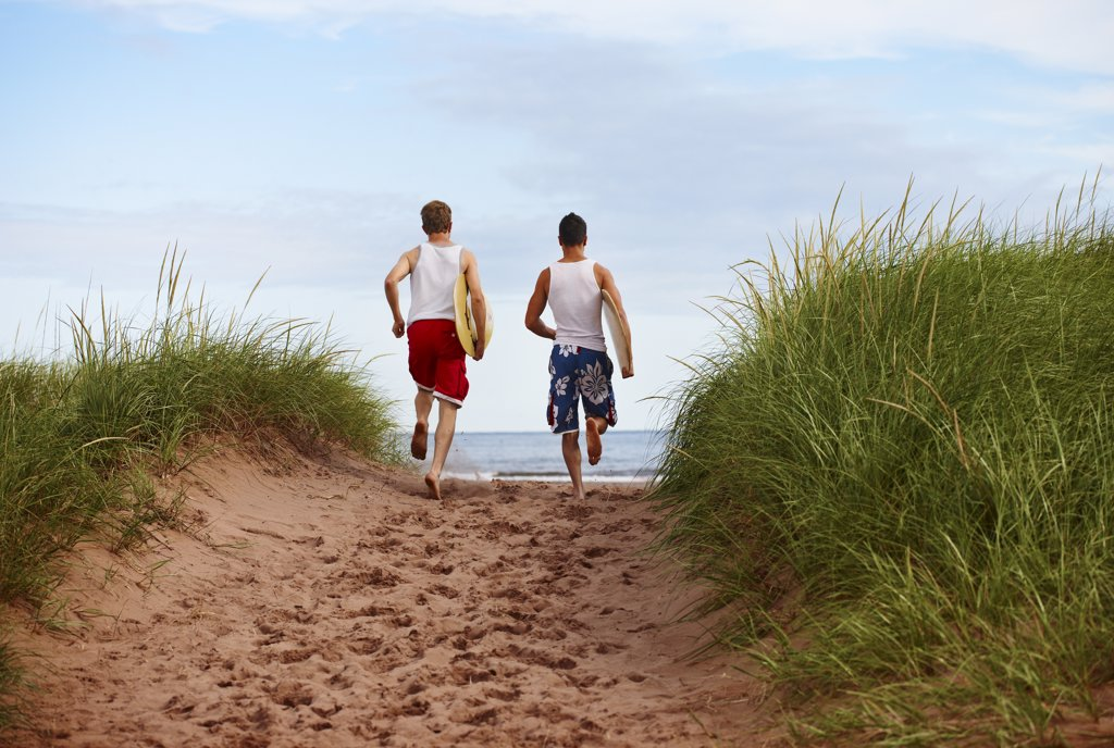 Young Men holding Skimboards while Running to Beach, PEI, Canada : Stock Photo