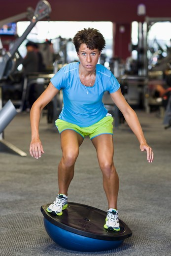 Woman using Balance Ball in Gym : Stock Photo