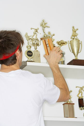 Stock Photo: 1828R-8760 Man Placing Trophies on Shelf