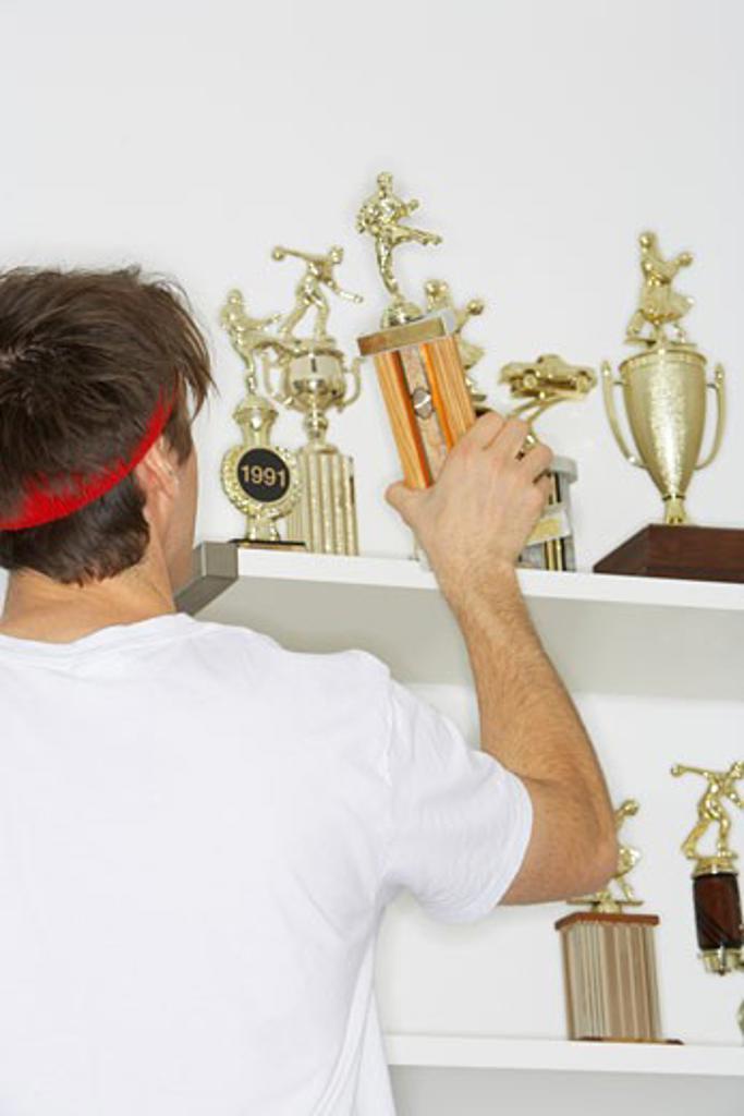 Man Placing Trophies on Shelf    : Stock Photo