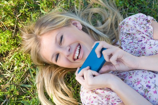Stock Photo: 1828R-88458 Close-up Portrait of Woman Lying on Grass holding Cell Phone