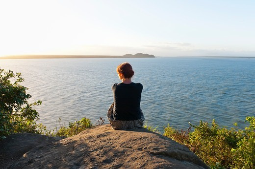 Stock Photo: 1828R-89004 Backview of Woman Sitting on Hill, Ilha do Mel, Parana, Brazil