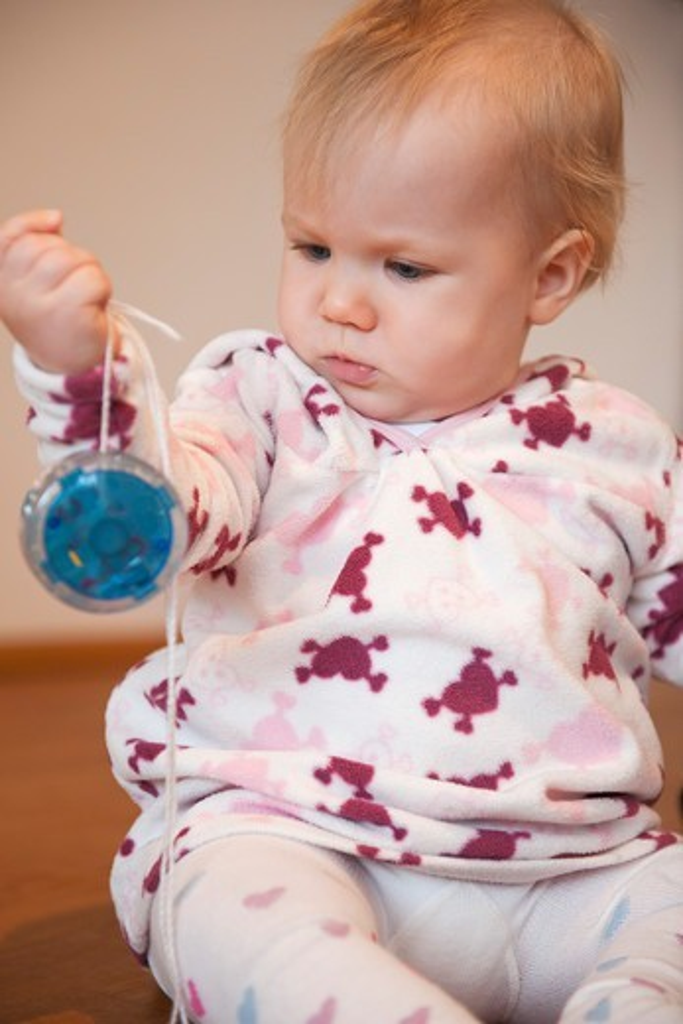 Stock Photo: 1828R-89215 Baby Girl Sitting on Floor Playing with Yo-Yo
