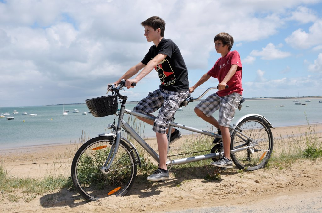 Stock Photo: 1828R-91493 Brothers Riding Tandem Bicycle on Beach, Ile de Re, France