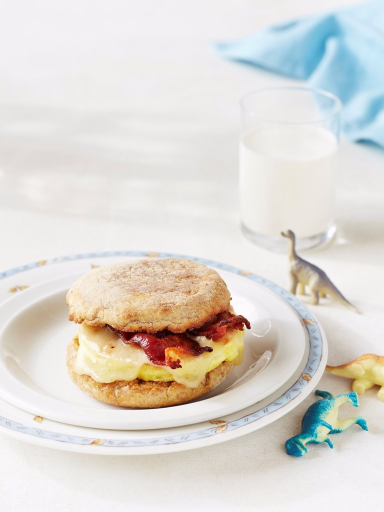 Scrambled Egg and Bacon on English Muffin with Toy Dinosaurs on Table : Stock Photo